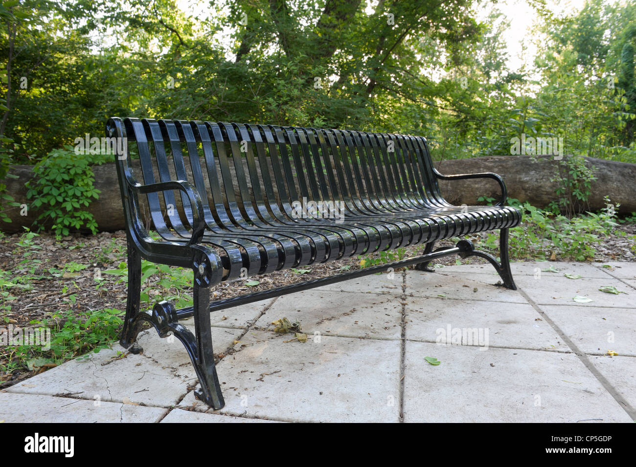 Glänzend schwarz Metall Parkbank auf einem Betonsockel vor Wald und ...