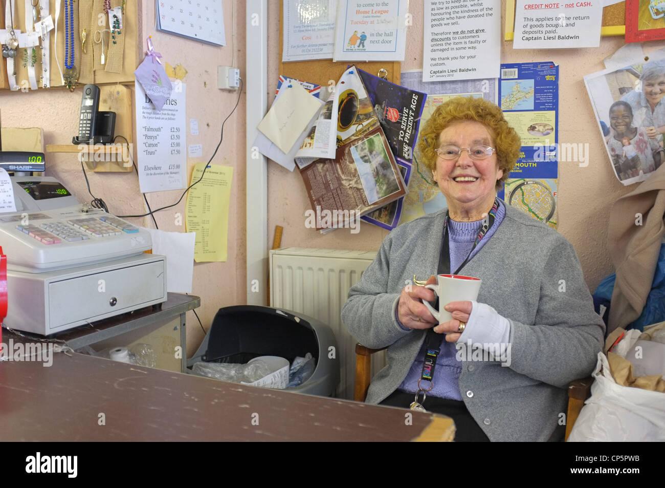 Ein Helfer in der Heilsarmee-Charity-Shop in Falmouth, Cornwall Stockbild