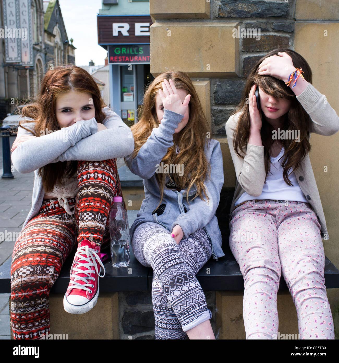 Drei Mädchen im Teenageralter zusammen draußen im Freien sitzen, die drei weisen Affen - nicht sprechen, Stockbild