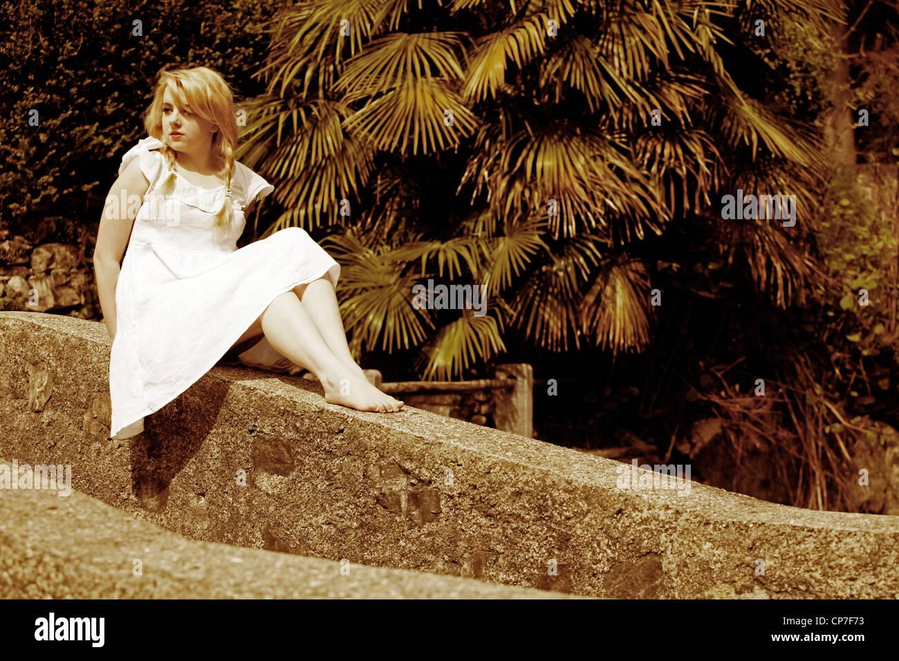 junge Frau mit Zöpfen sitzt auf einer Wand in einem weißen Kleid Stockbild