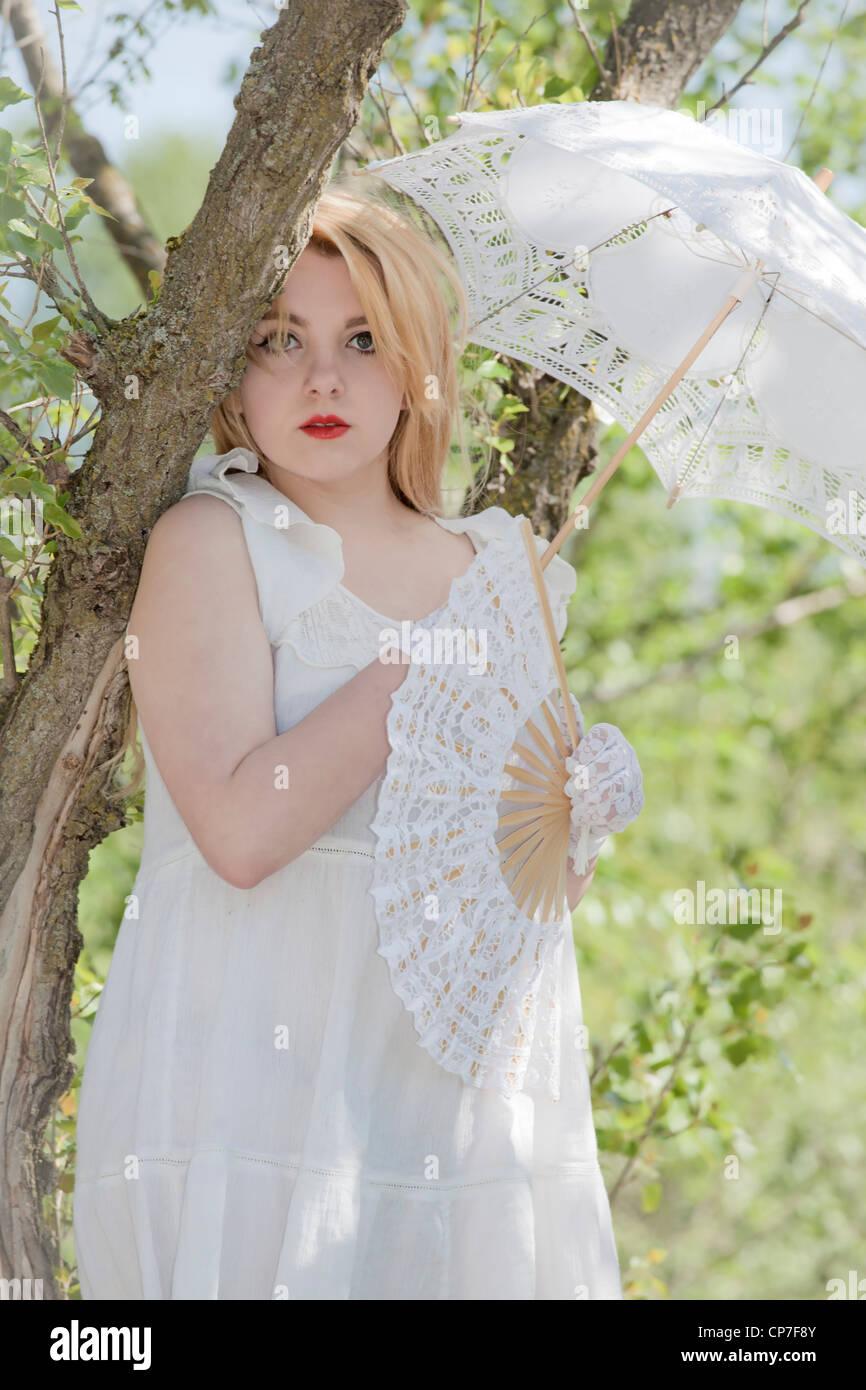 junge Frau im weißen Kleid mit einem Sonnenschirm und Ventilator im Wald Stockfoto