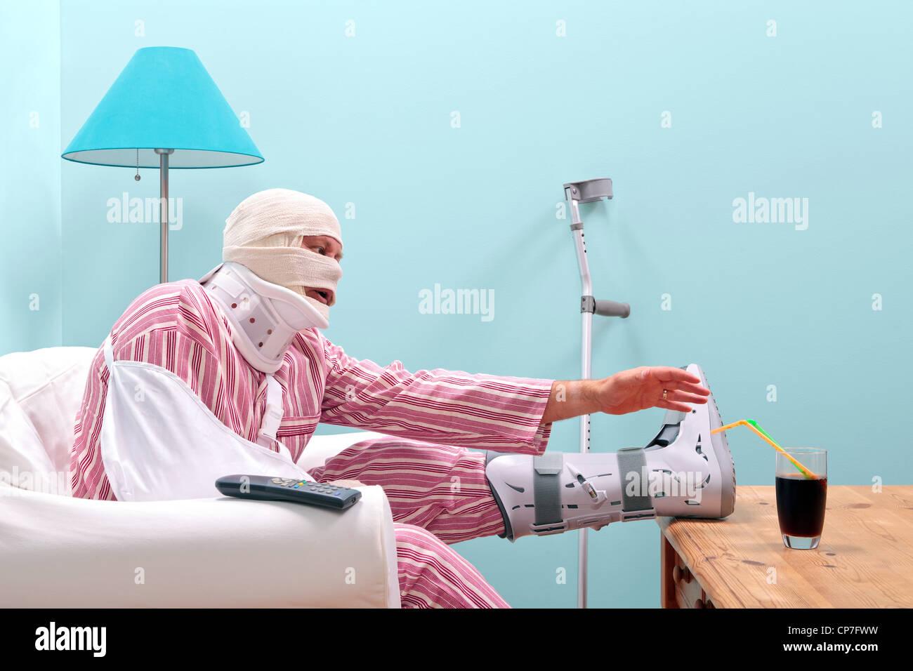 Foto von einem verletzten Mann im Pyjama mit bandagiertem Kopf, Gipsbein, Arm Schlinge und Hals Korsett Stockbild
