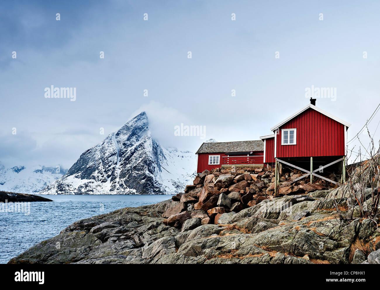 Eine Rorbu (Fischer Hütte, jetzt als Ferienunterkunft genutzt) bei Hamnoy mit Olstind Berg im Hintergrund Stockbild