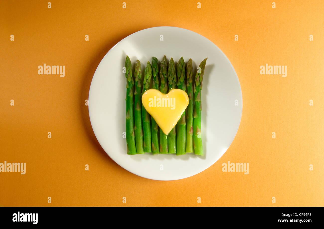 Butter-Herzen schmelzen auf Spargelspitzen Stockbild