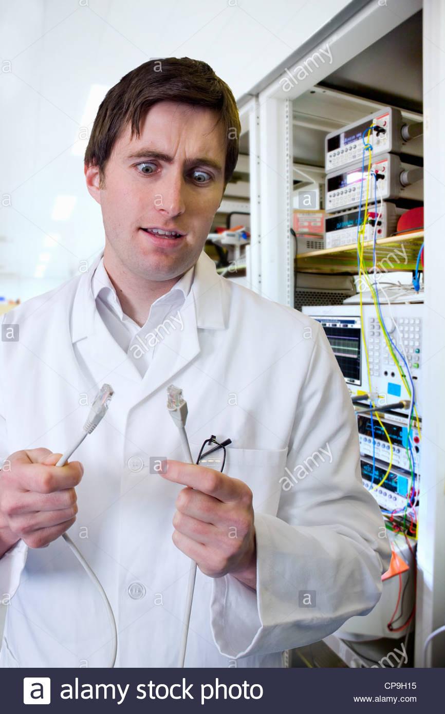 Mit weit aufgerissenen Augen Ingenieur mit Daten-Kabel vom Computer im Labor Stockbild