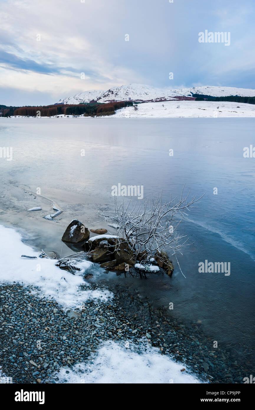 Eine gefrorene Clatteringshaw Loch mit Craignell in der Ferne in Winter, Galloway Forest Park, Galloway, Scotland, Stockbild