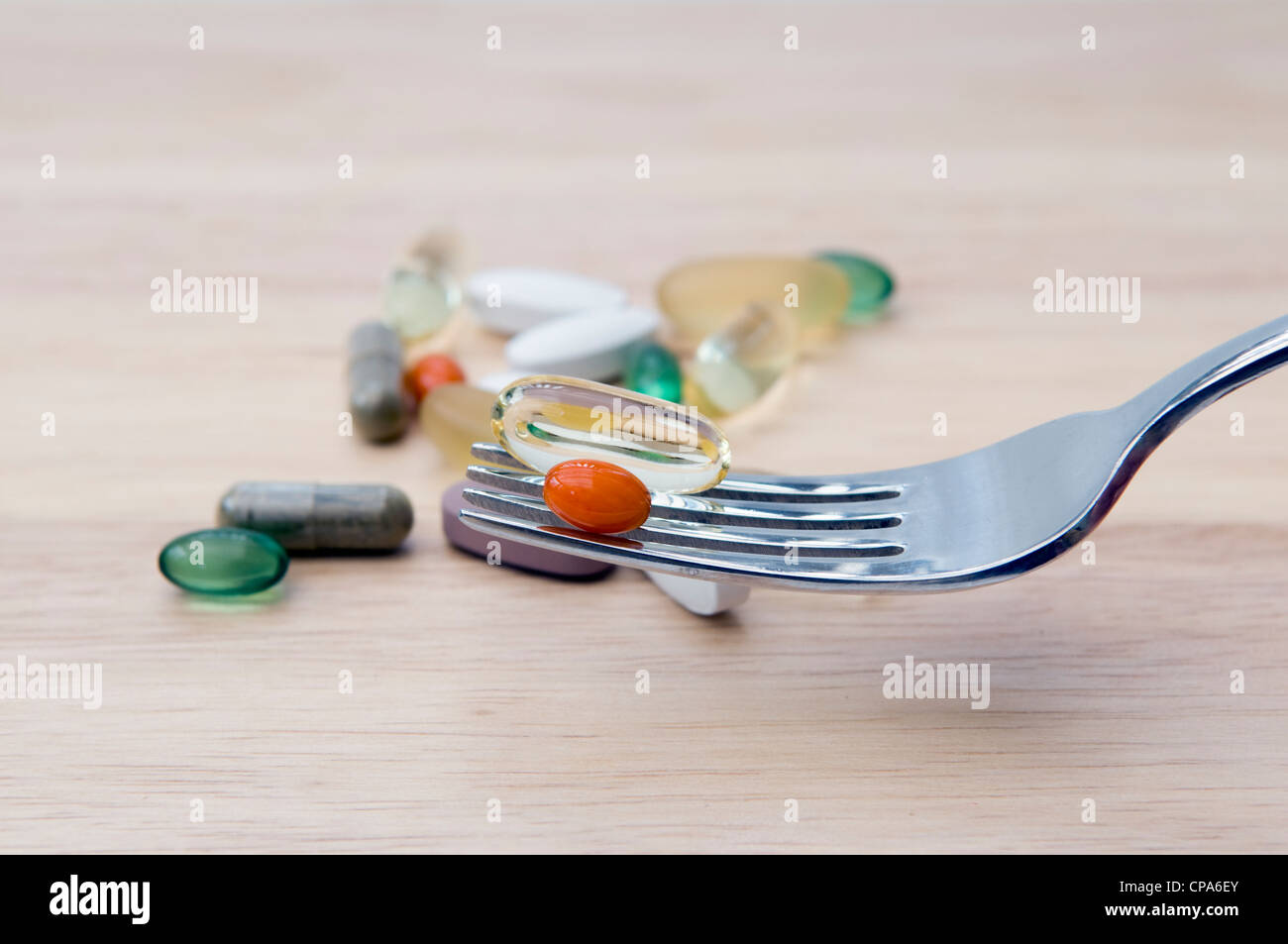 Auswahl an Vitaminen (Omega-3, Co-Enzym Q10, Pfefferminze, Chondroitin, Ginkgo und Ginseng) auf Gabel und Schneidbrett Stockbild