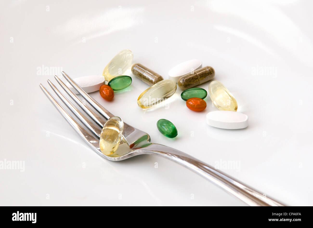 Auswahl an Vitaminen (Omega-3, Co-Enzym Q10, Pfefferminze, Chondroitin, Ginkgo und Ginseng) mit Gabel auf weißem Stockbild