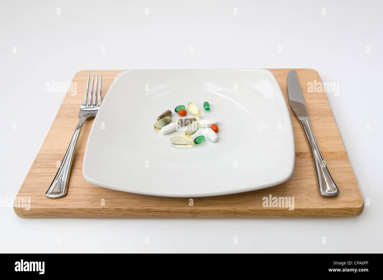 Abendessen mit einer Auswahl an Vitaminen (Omega-3, Co-Enzym Q10, Pfefferminze, Chondroitin, Ginkgo und Ginseng) Stockbild