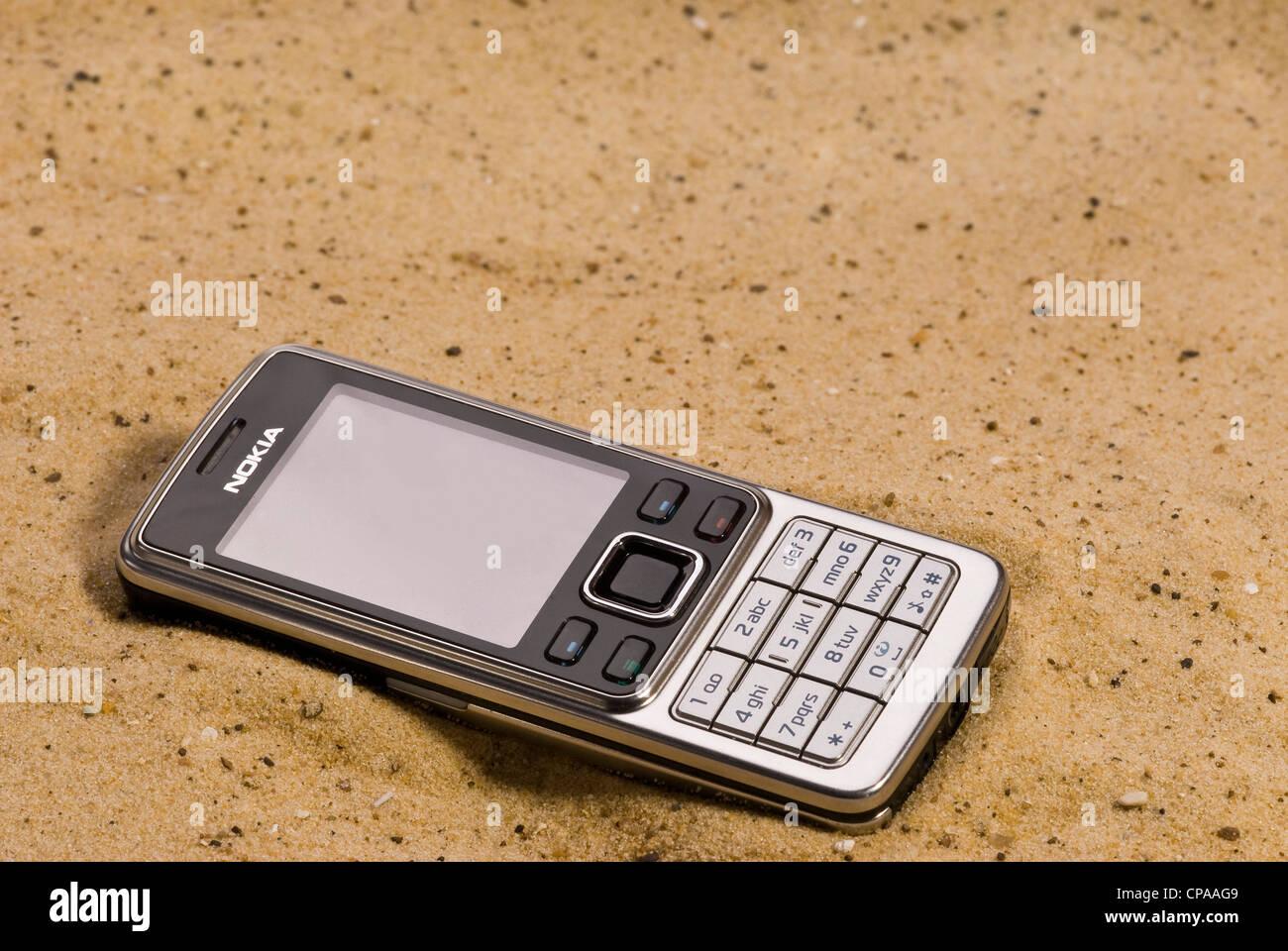 Handy fiel und Verlegung in den Sand am Strand. Verloren fehl am Platz Stockbild