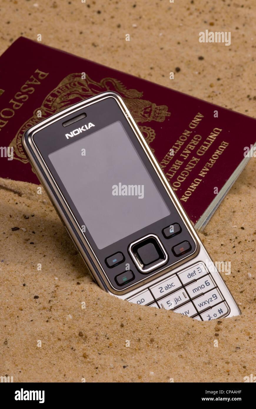 Verlorenen Reisepass und Mobiltelefon in den Sand zu legen. Stockbild