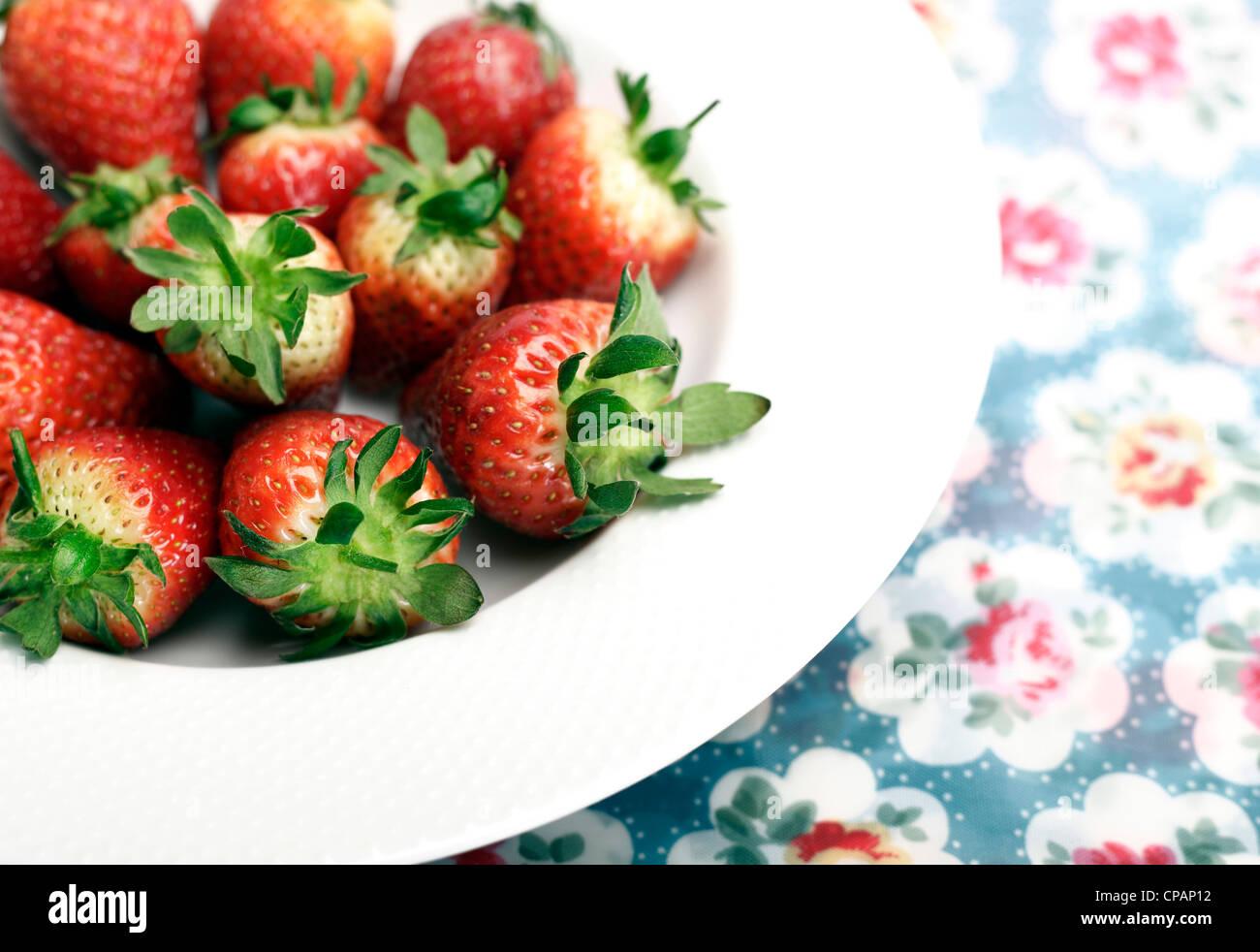 Schale mit Erdbeeren auf einer floral Tischdecke Stockbild