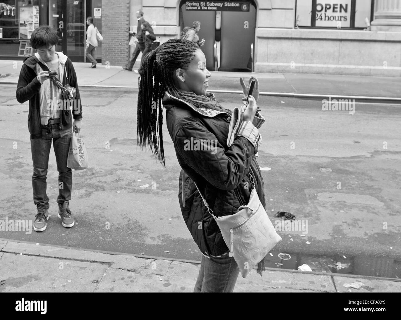 Eine Frau benutzt ihr Handy ein Foto zu machen, während jemand anderes sein Telefon für Nachrichten überprüft. Stockfoto
