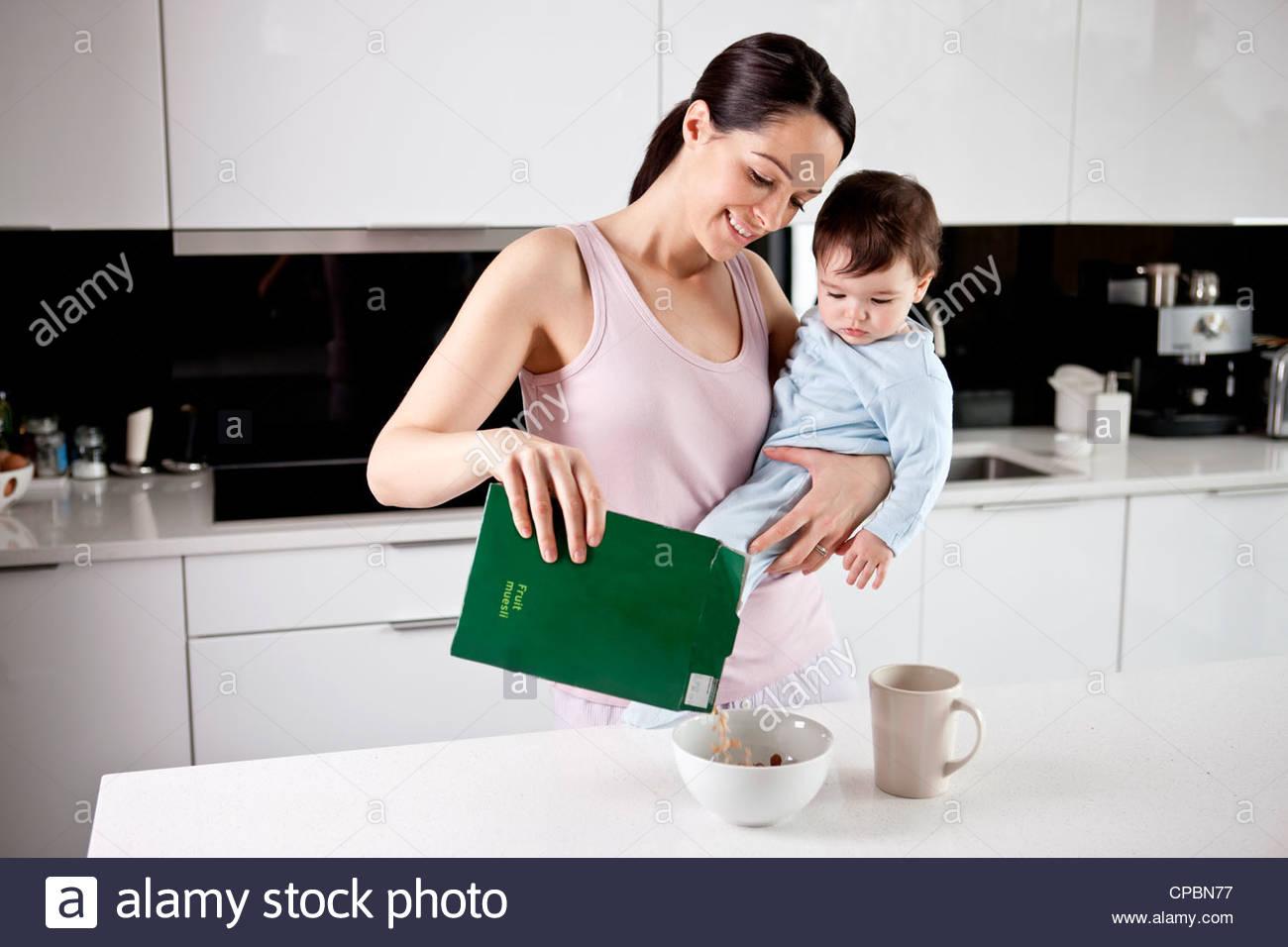 Eine junge Mutter hält ihr Baby Sohn während Frühstück Stockbild