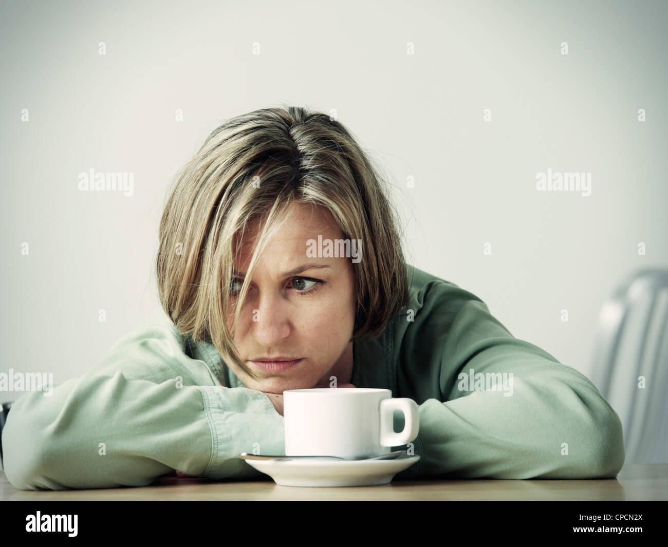 Frau ruhen Kopf in Händen am Schreibtisch Stockbild