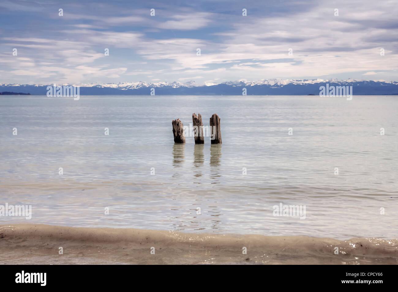 drei gebrochene Holzpfähle im Bodensee, Blick auf die Santis Stockbild