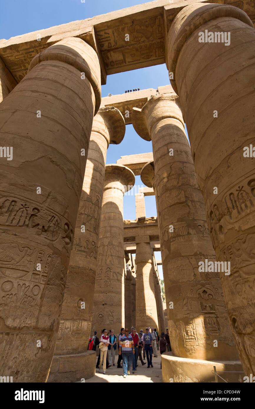 Touristen, die in den Schatten gestellt durch die hoch aufragenden Säulen der großen Säulenhalle Stockbild