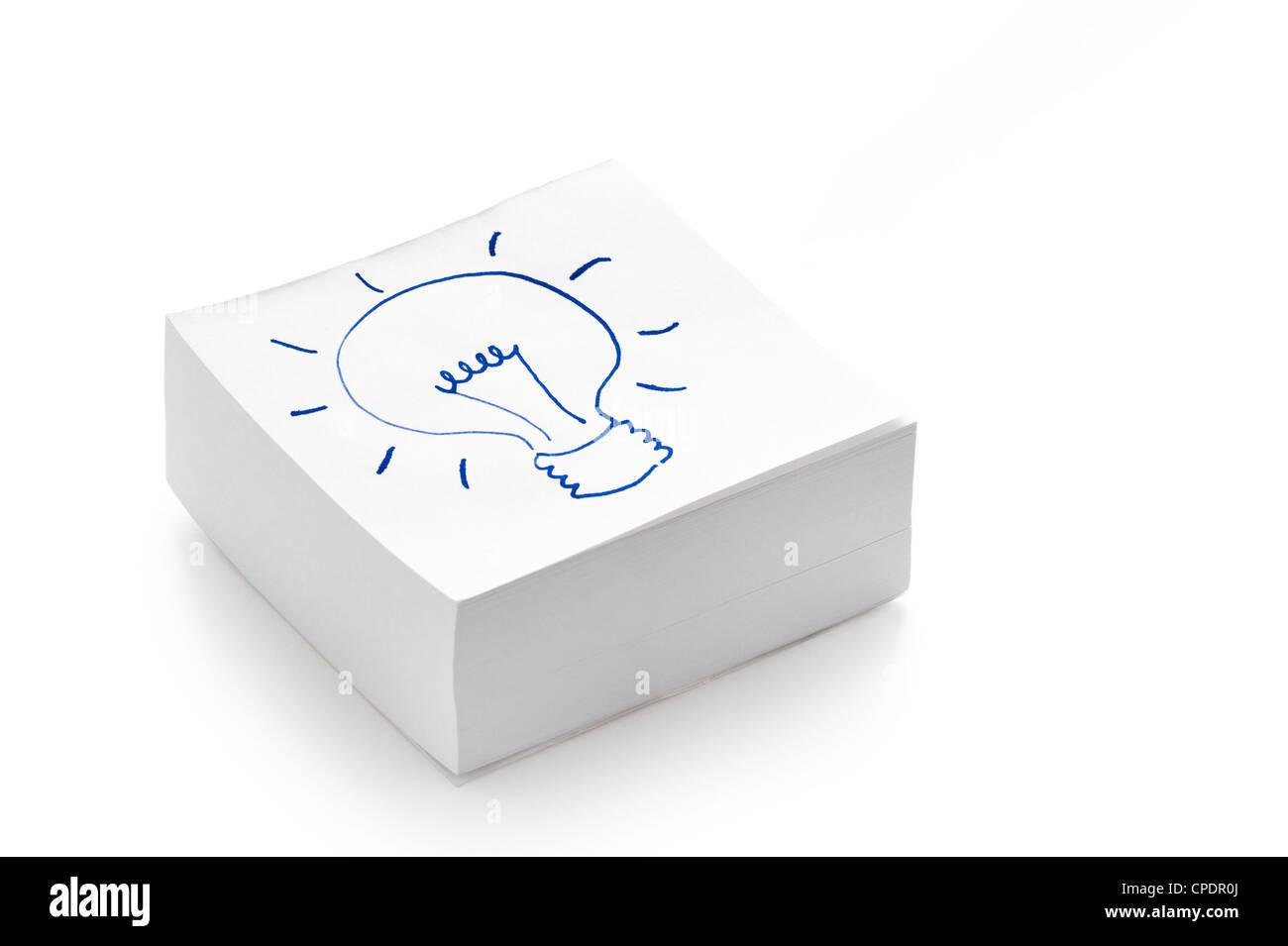 Glühbirne, die Zeichnung auf einen Stapel Post es Notizen illustriert das Konzept des Habens einer Idee Stockbild