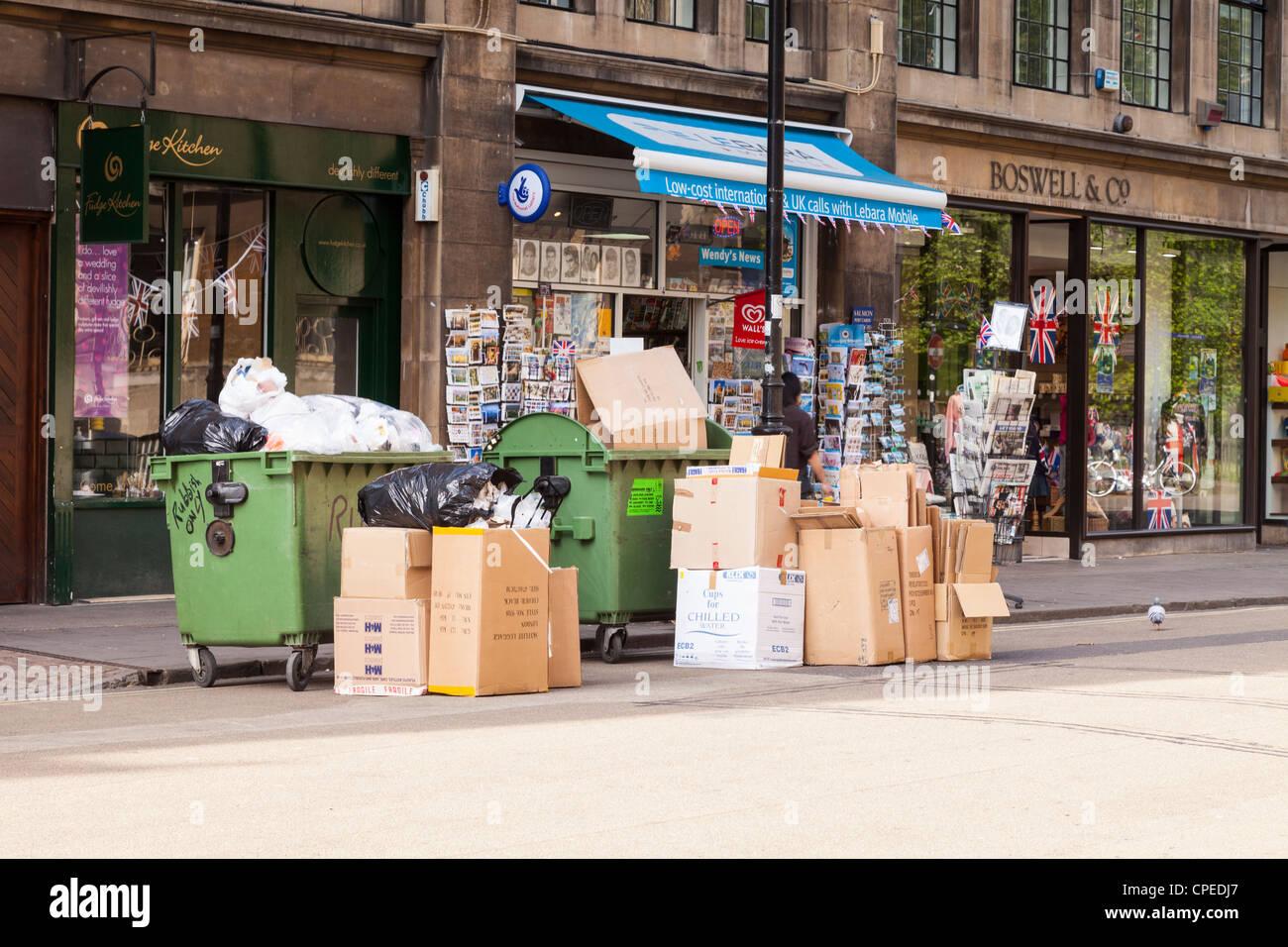 Zwei Sprünge und mehrere Kartons von Müll oder Abfall warten an den Bordstein für Sammlung, Broad Stockbild