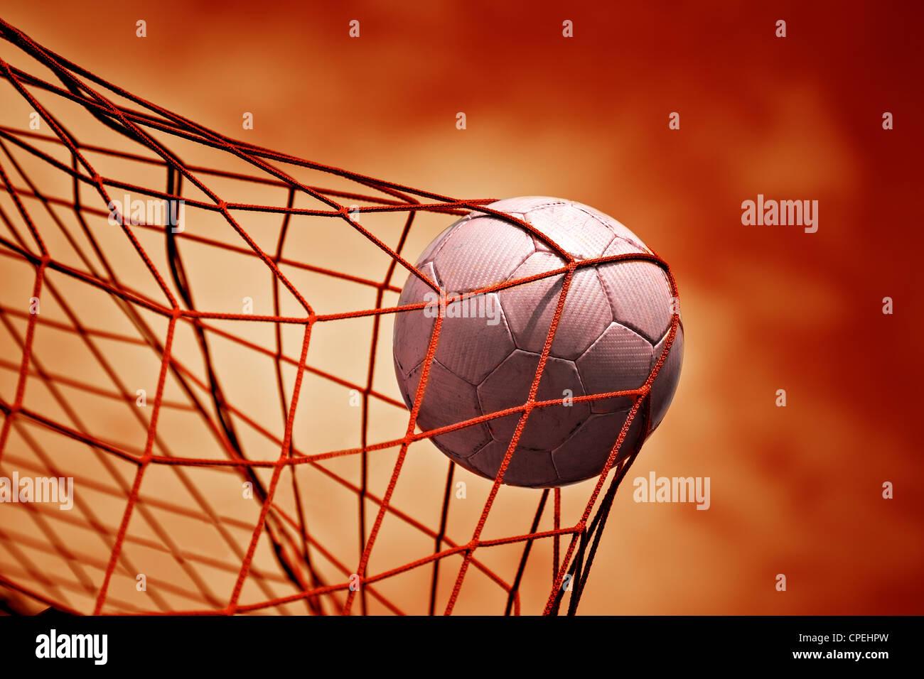 symbolisches Bild für Ziel mit einem Fußball im Netz Stockbild