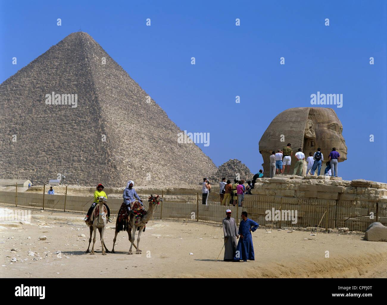 Ägypten. Kairo. Gizeh. Touristen und Kamele. Pyramide und Sphinx. Stockfoto