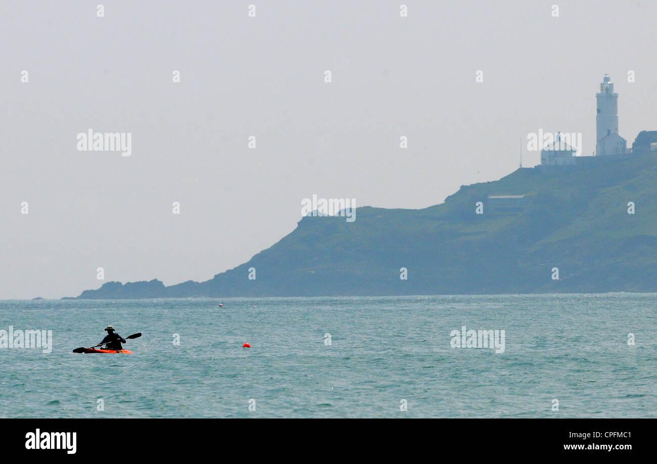 Ein Kajakfahrer Paddel über Start Bucht mit Startpunkt und Start Point Leuchtturm im Hintergrund. Stockfoto