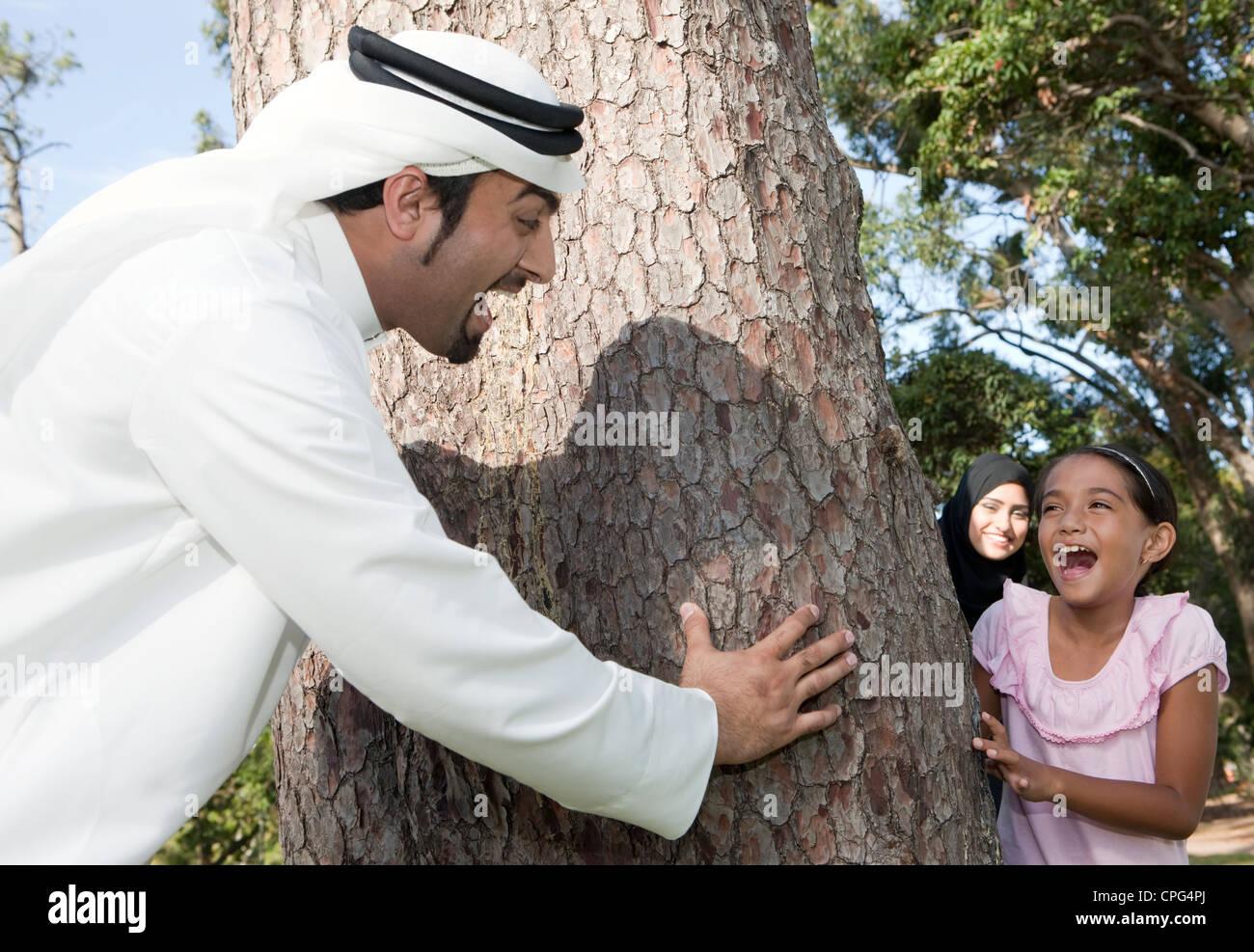 Arabische Familie spielen Versteckspiel im Park. Stockbild