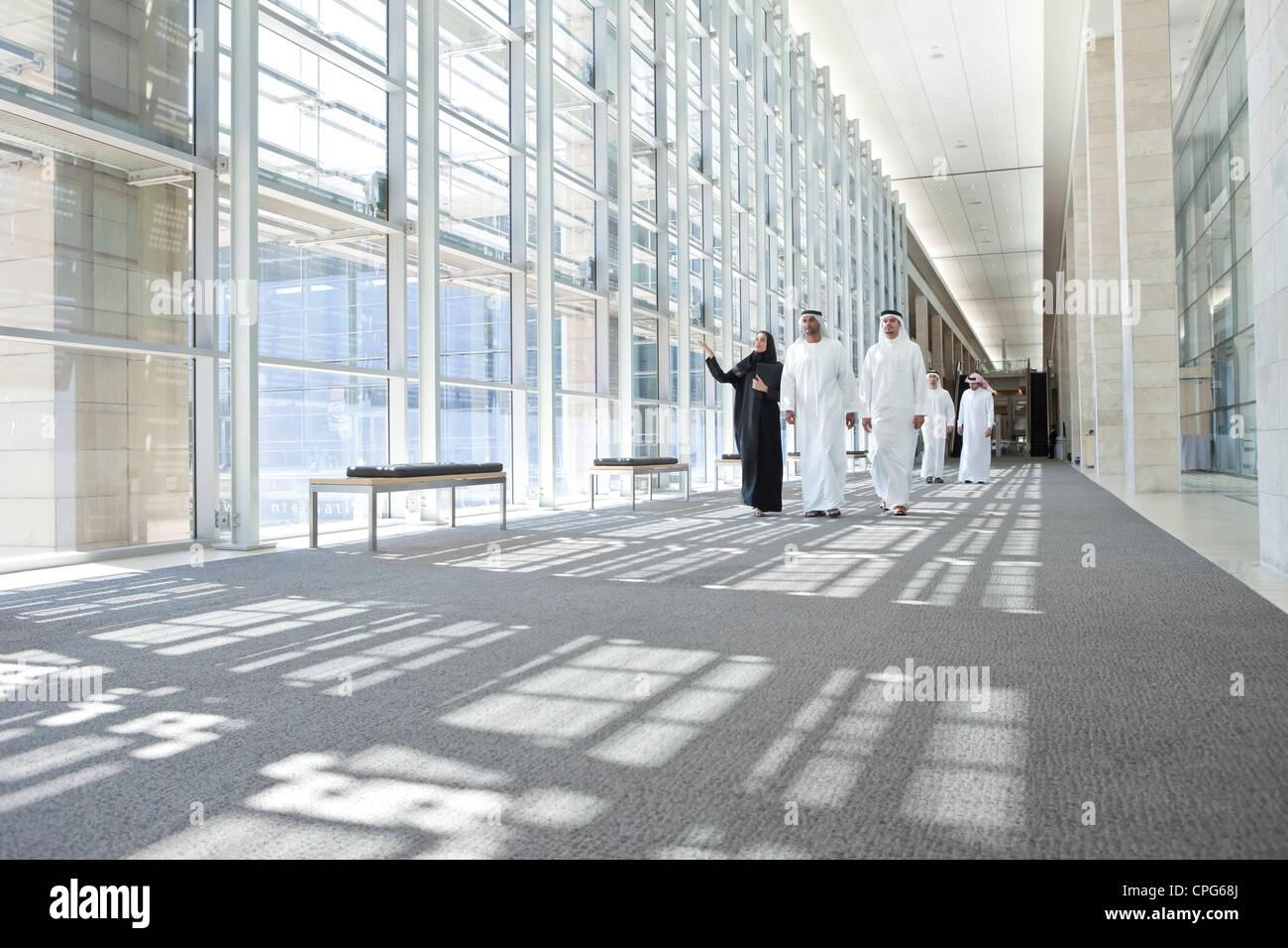 Geschäftsleute sprechen während des Gehens auf dem Büro-Flur. Stockbild