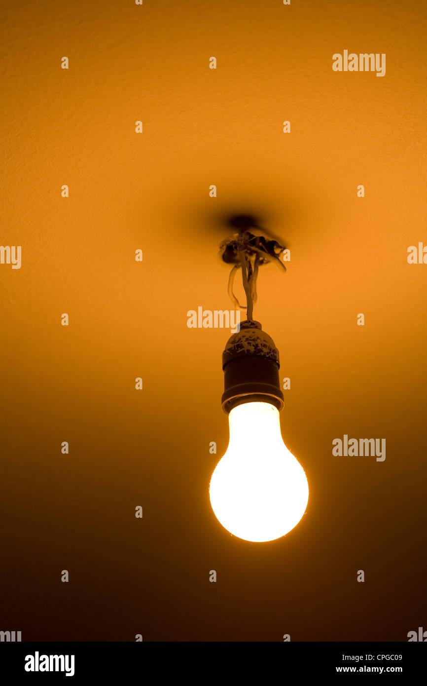Nackte Glühbirne an der Decke Stockbild
