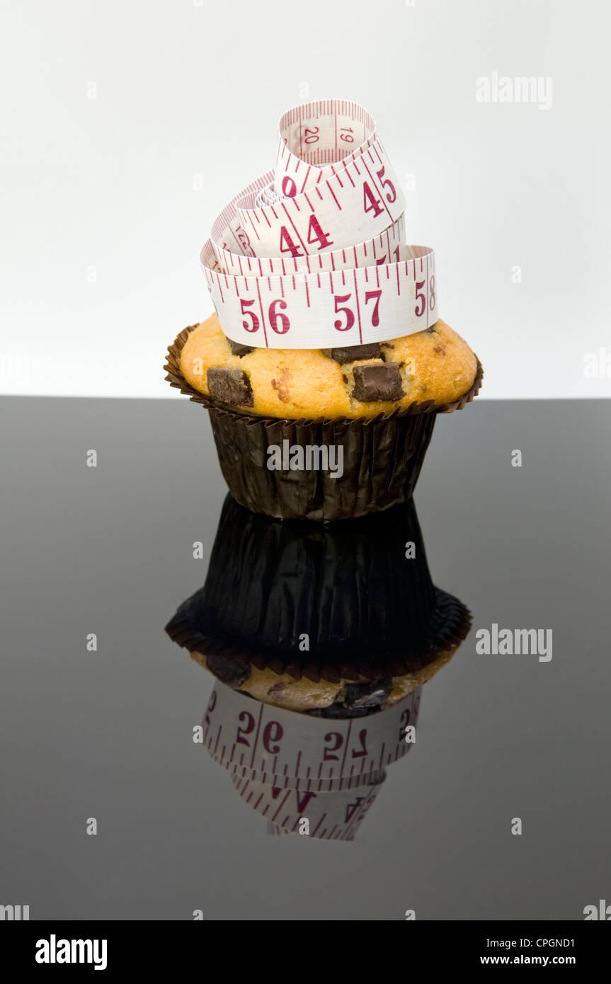 Chocolate Chip Muffins mit Maßband und Reflexion mit Konzept, das Essen Kuchen auf den Zoll anhäufen wird Stockbild