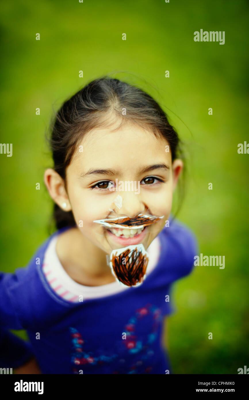 Movember. Mädchen mit ihren hausgemachten Schnurrbart und Bart, der sie ihr Gesicht mit Klebeband gesteckt Stockbild