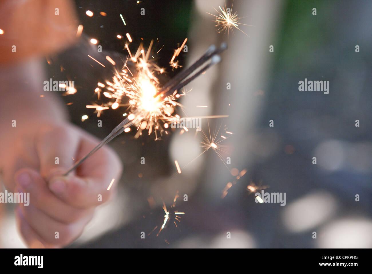 Nahaufnahme eines Kindes halten mehrere Wunderkerzen brennen. Stockbild