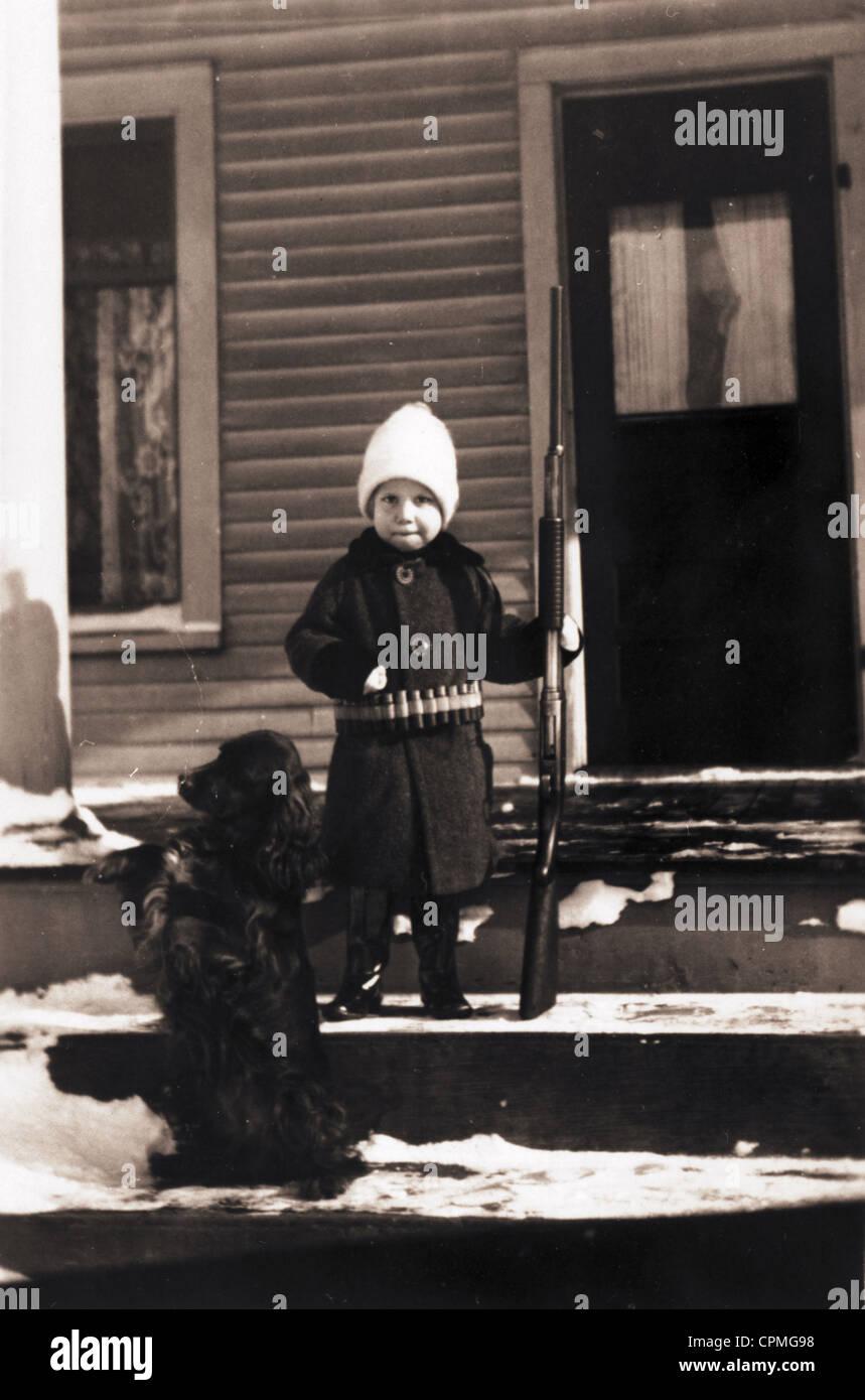 Schwer bewaffnet, Little Boy & Hund Wache Homestead Stockbild