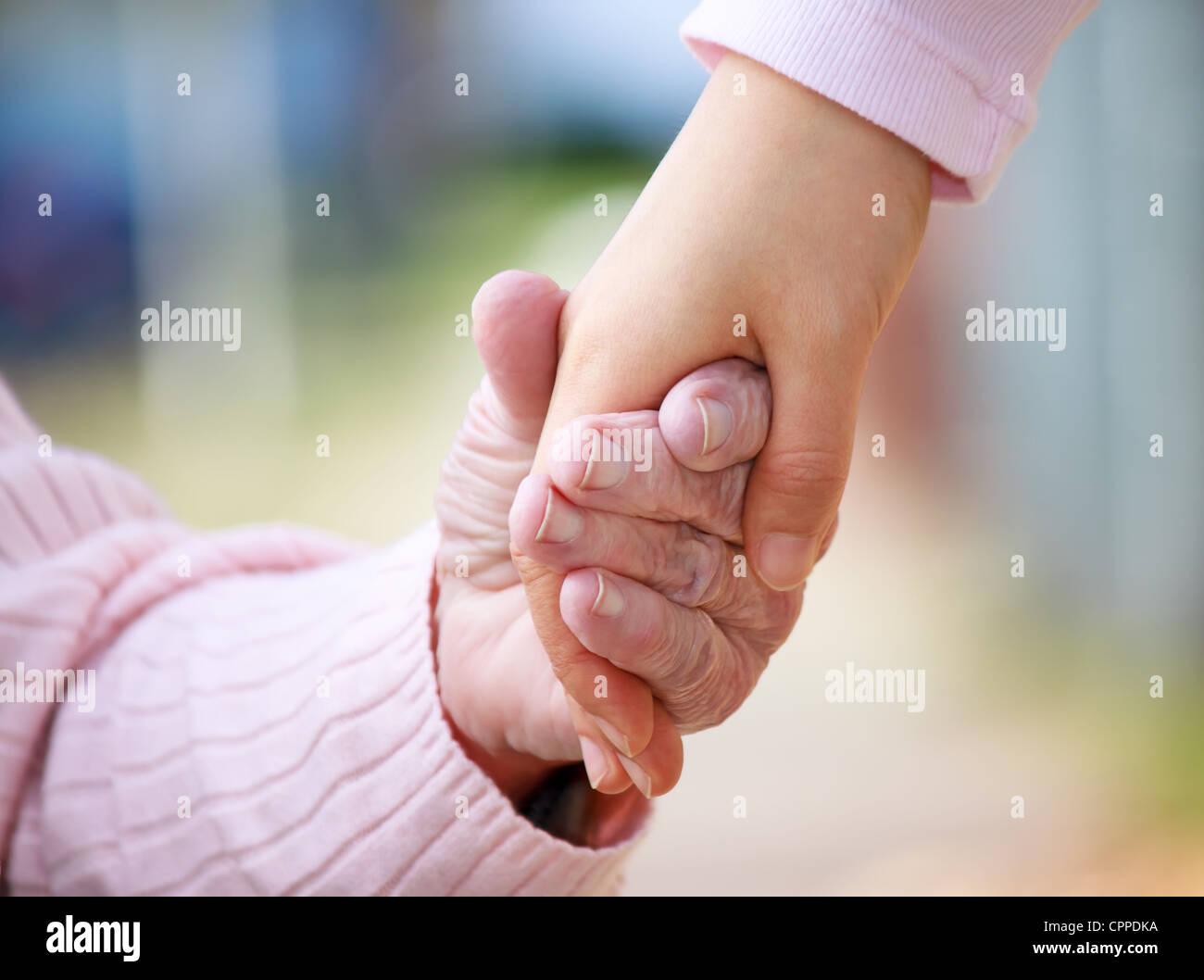 Ältere Frau durchlöchern Hände mit jungen Hausmeister Stockfoto