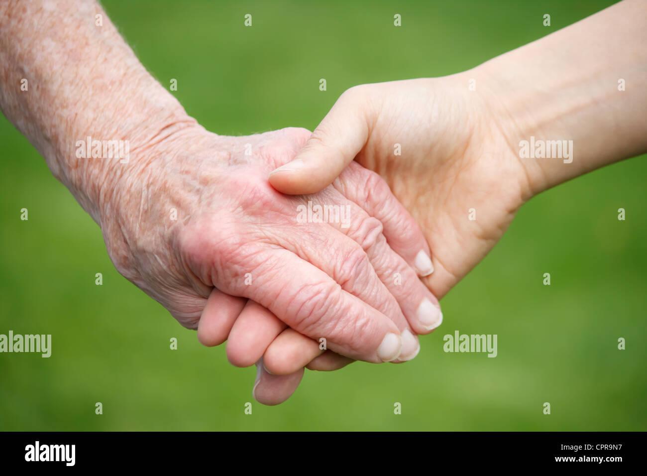 Ältere Dame und junge Frau, die Hand in Hand Stockbild