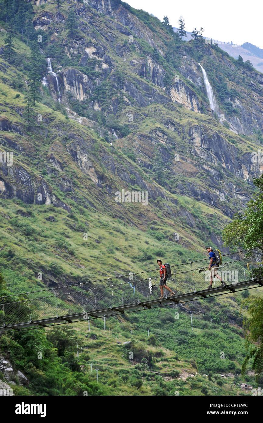 Wanderer durchqueren eine 60 Meter lange Hängebrücke, nördlich von Tal, Bhulbhule, Nepal Stockbild