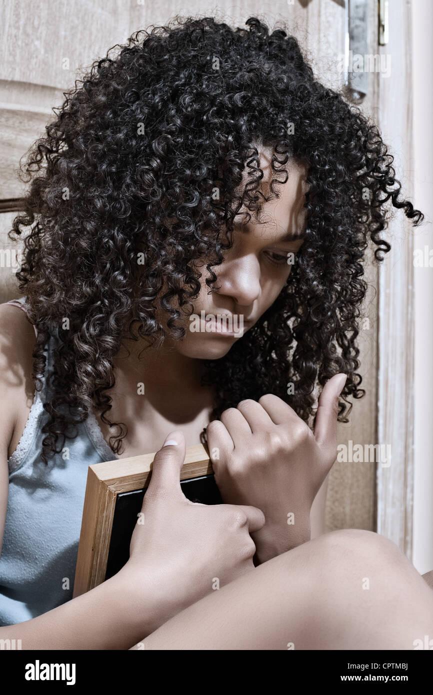 Junge Frau mit dem Rücken zu einer Tür umklammert ein gerahmtes Bild Stockbild