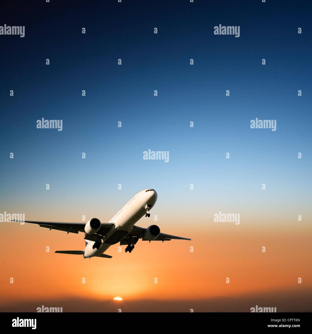 Boeing 777 kommen, um bei Sonnenuntergang zu landen. Stockbild