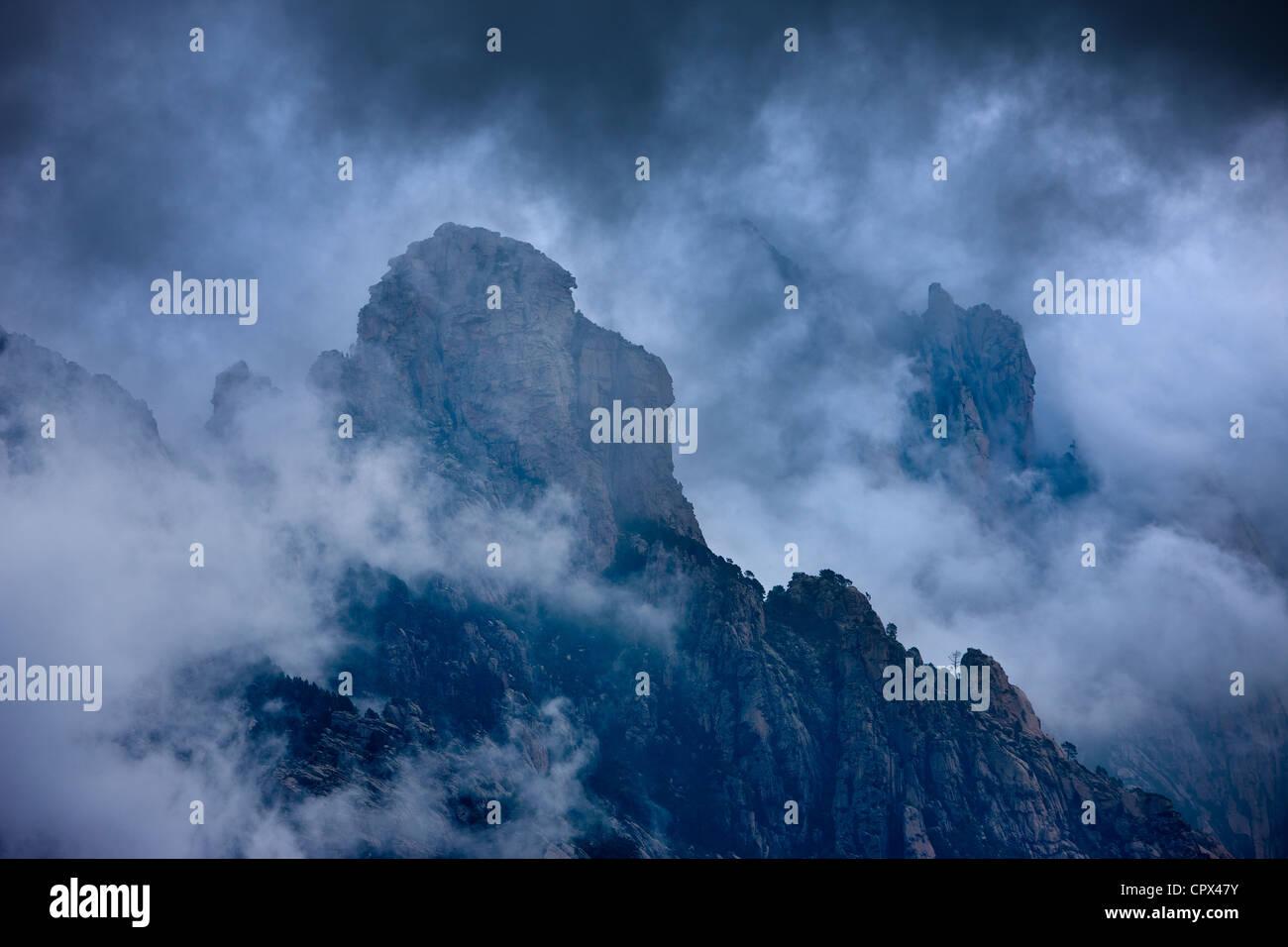 Regenwolken hängen über den Col de Bavella, Berge Bavella, Korsika, Frankreich Stockbild