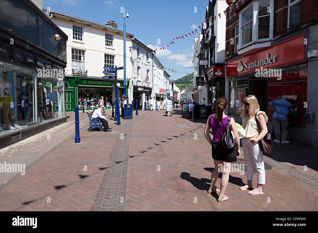 Stehen die Leute reden eine Fußgängerzone Abschnitt der wichtigsten shopping Street, Abergavenny, Wales, Stockbild