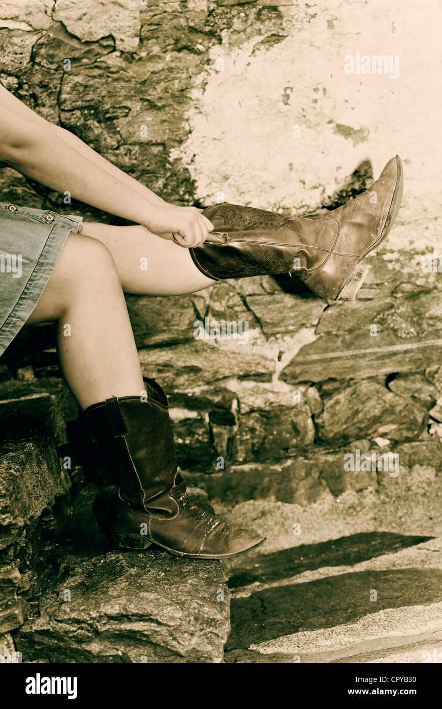 Beine einer jungen Frau im Jeansrock und Cowboy-Stiefel Stockbild