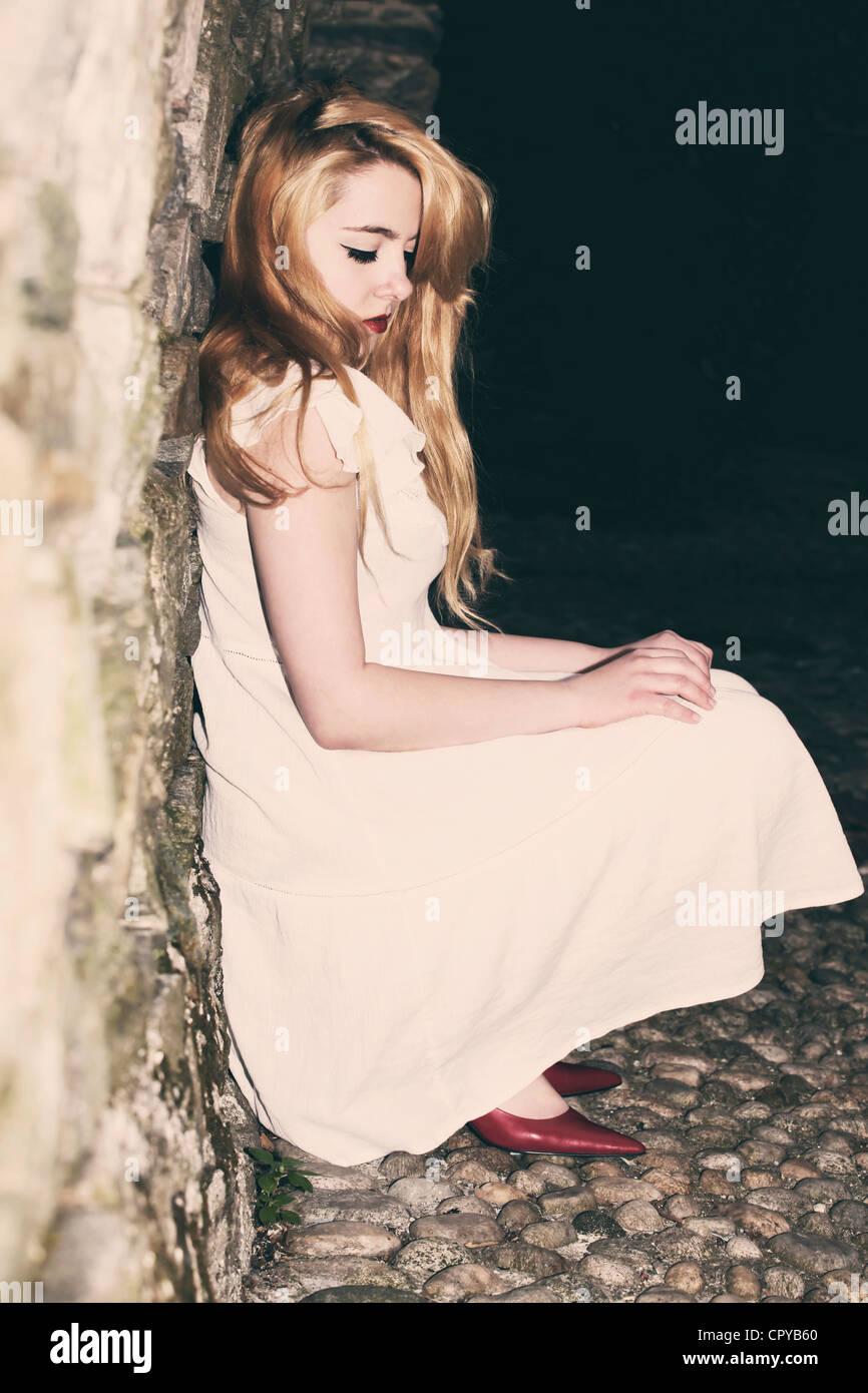 junge Frau sitzt in einer dunklen Gasse, an eine Wand gelehnt Stockbild