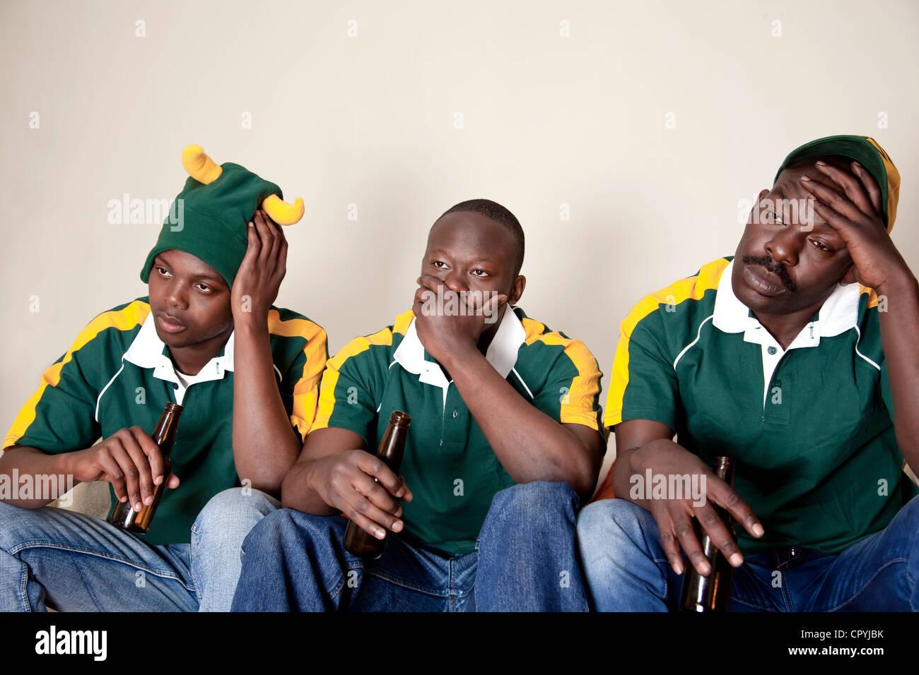 Drei Freunde in Rugby-Uniformen gekleidet eine Rugby-Spiel im Fernsehen zu sehen, beim Bier trinken Stockbild