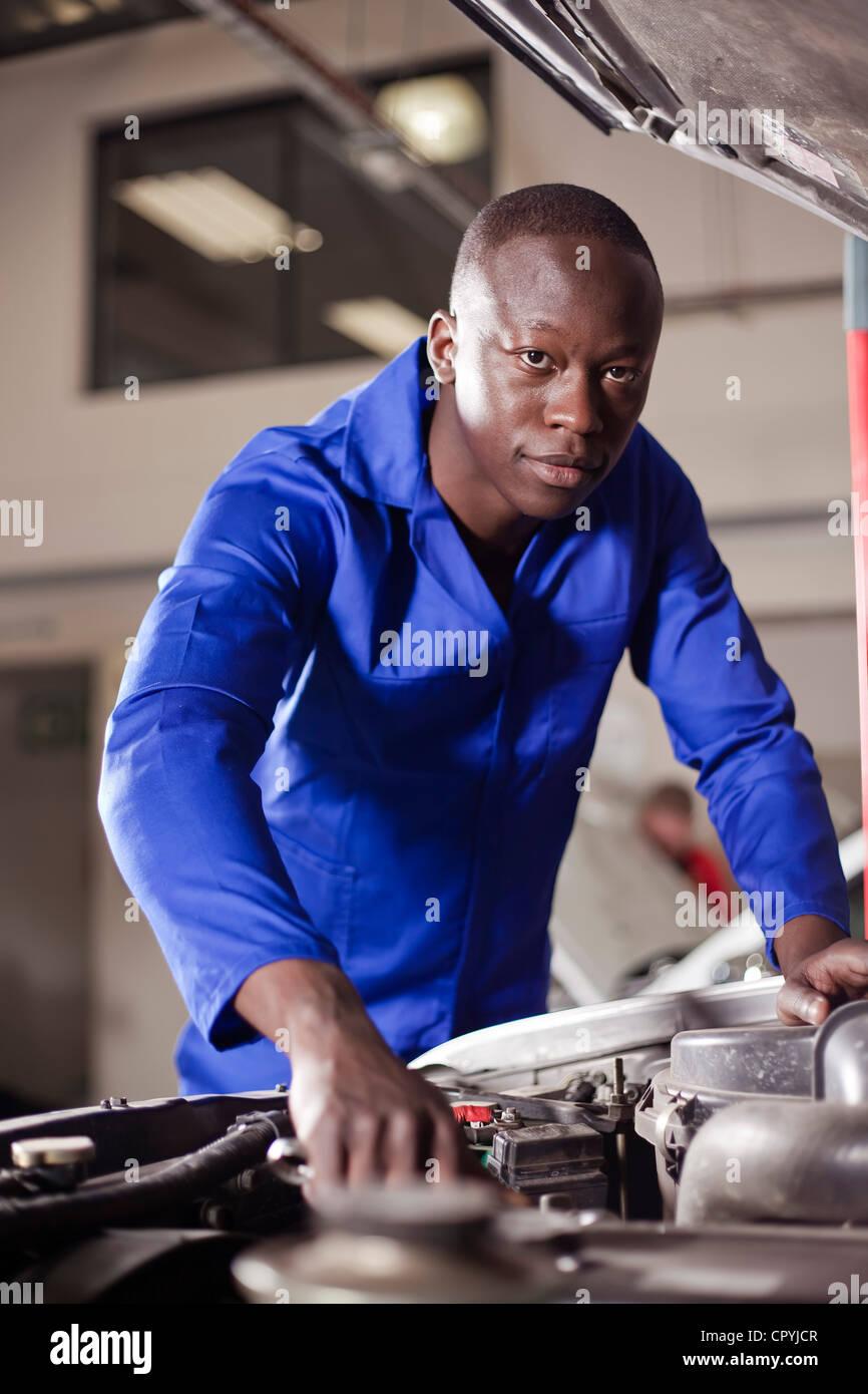 Afrikanischer Mann arbeitet an einem Automotor Stockbild