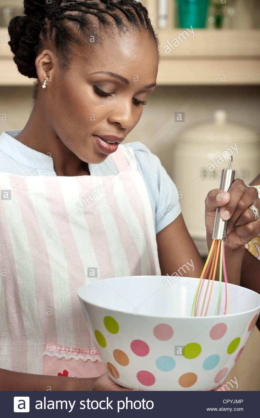 Afrikanische Frau schlagen in einer Küche Stockbild