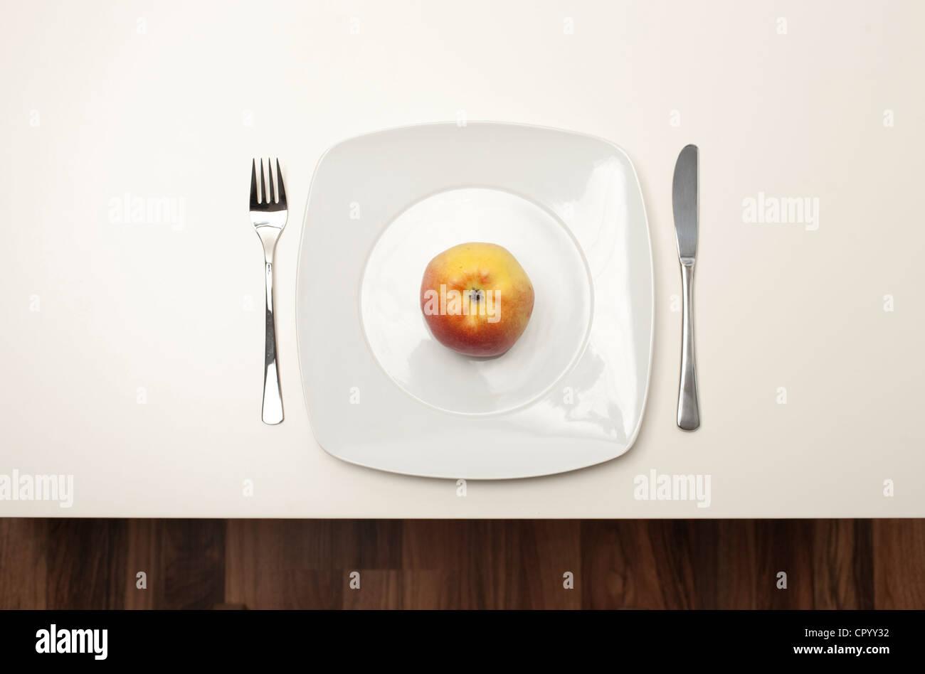 Apple auf einem weißen Teller Stockfoto
