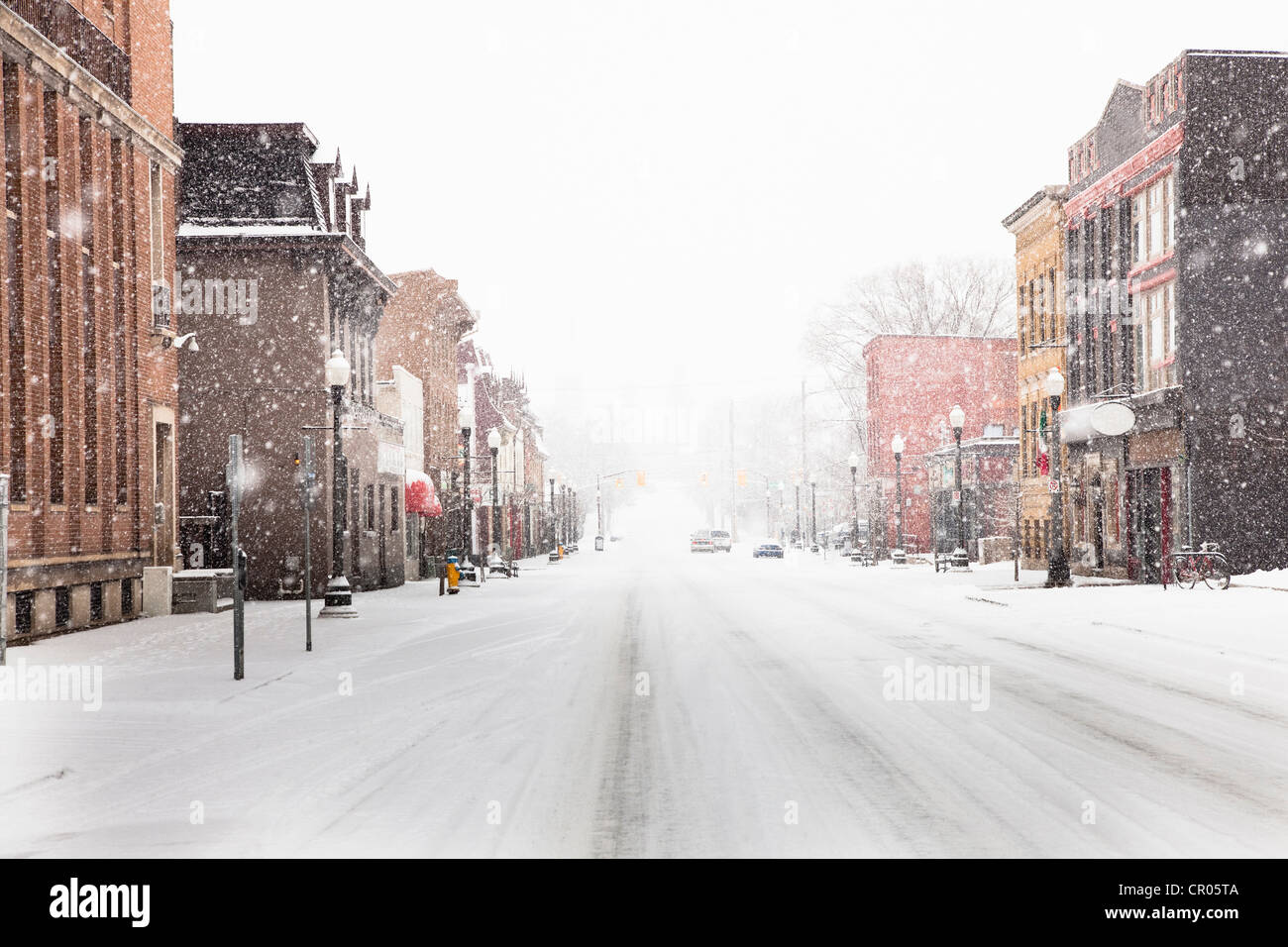 Schnee fällt auf Stadtstraße Stockbild