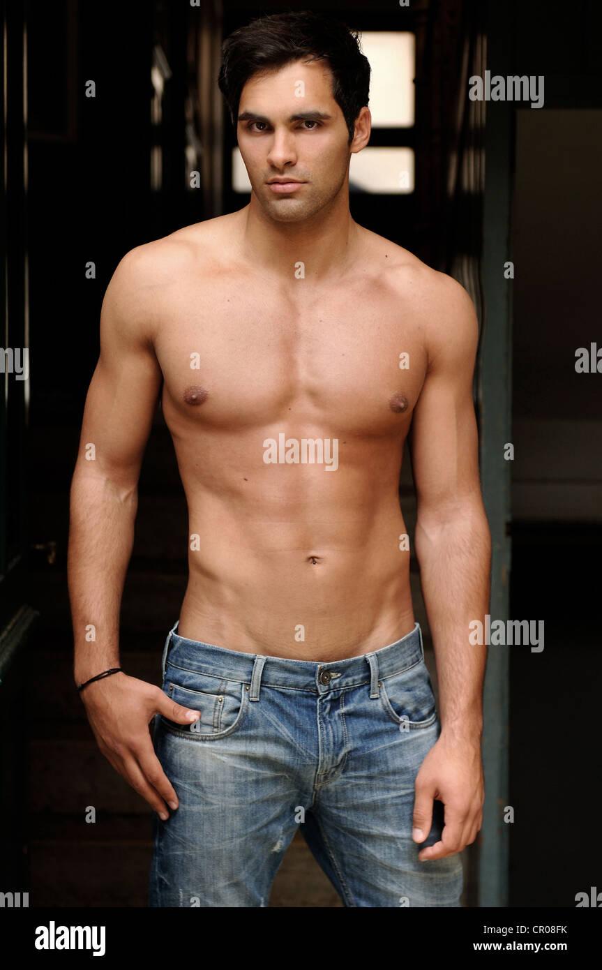 21 Jahre alten mediterranen aussehenden Mann, trägt Jeans, nackten Oberkörper, im Korridor Stockbild