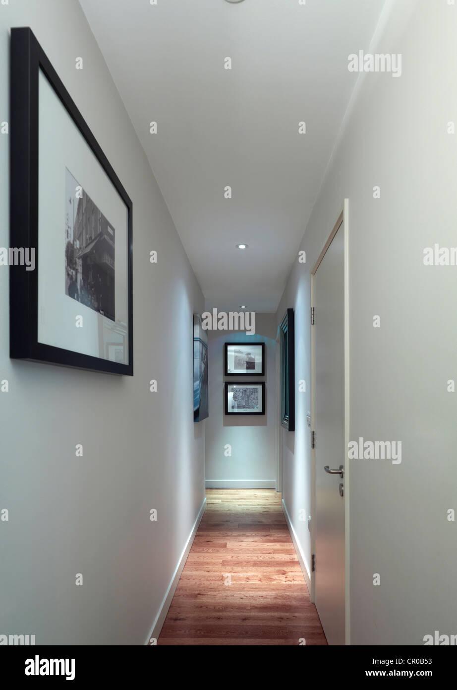 langen Korridor mit Parkettboden und weiße Wände mit Bildern hängen Stockbild