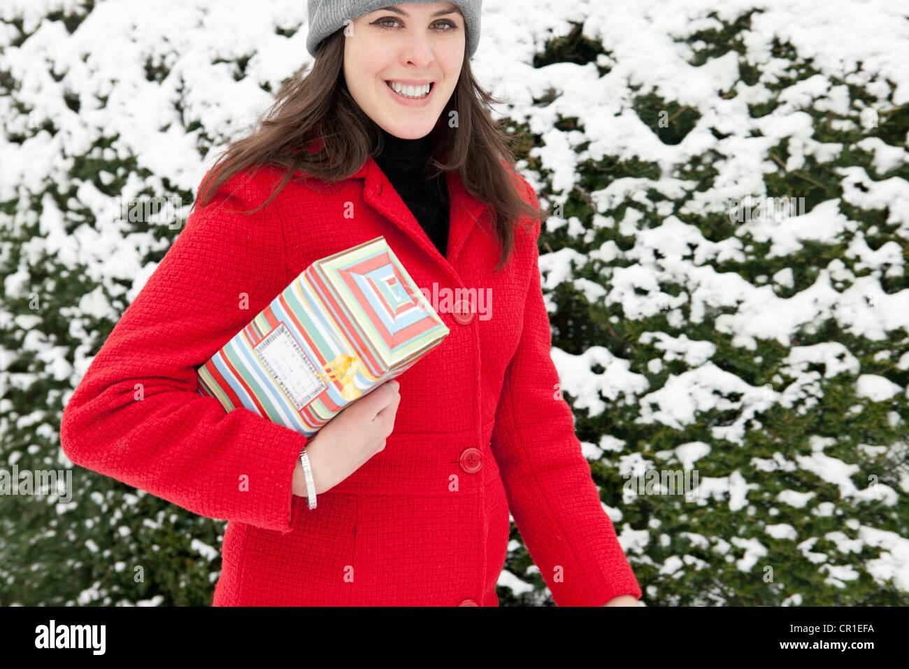 Frau mit Geschenk in Schnee gehüllt Stockbild